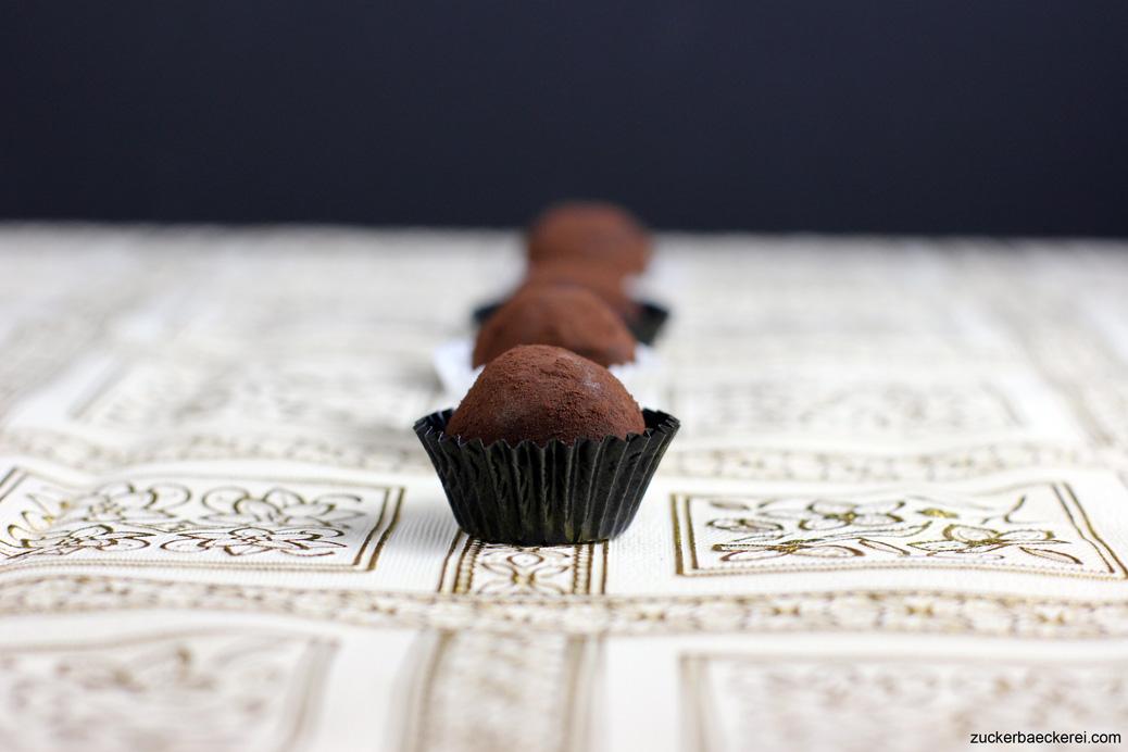 pralinen in schwarzen papierförmchen auf golden gemusterter Tischdecke