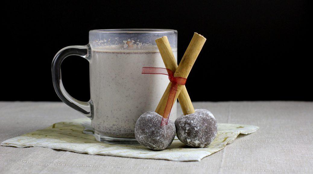zwei schokokugeln mit zimtstangen-stiel vor einer glastasse mit heißer schokolade