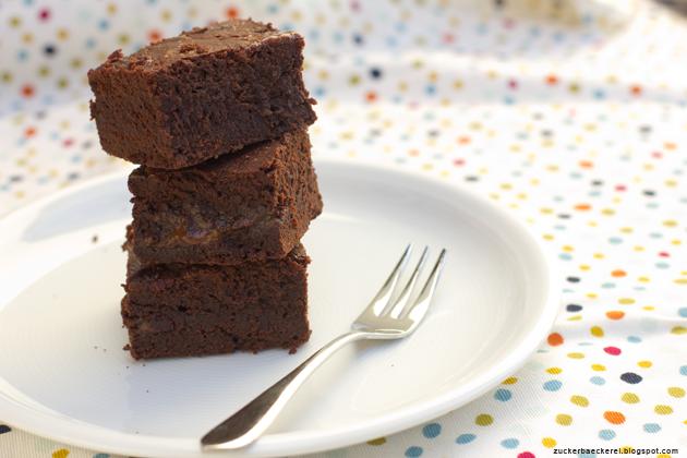 drei Stück brownies, gestapelt auf einem teller, darunter eine gepunktete tischdecke