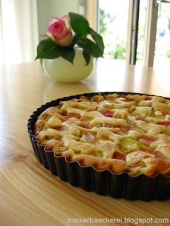tarteform mit rhabarberkuchen, eine vase mit rose im hintergrund
