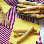 Brioche-Stangerl in einer box auf einer rot-weiß-gestreiften picknickdecke und gelben servietten