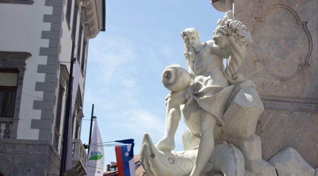 weiße statue an einem brunnen vor blauem himmel
