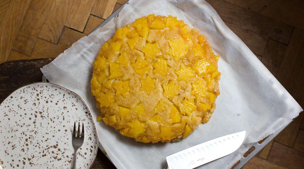 ananas tarte tatin von oben neben einem goldgesprenkelten teller und einem messer