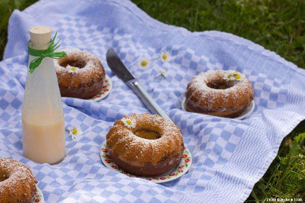 vier guglhupfs und eine eierlikörflasche auf einer blauen tischdecke im gras