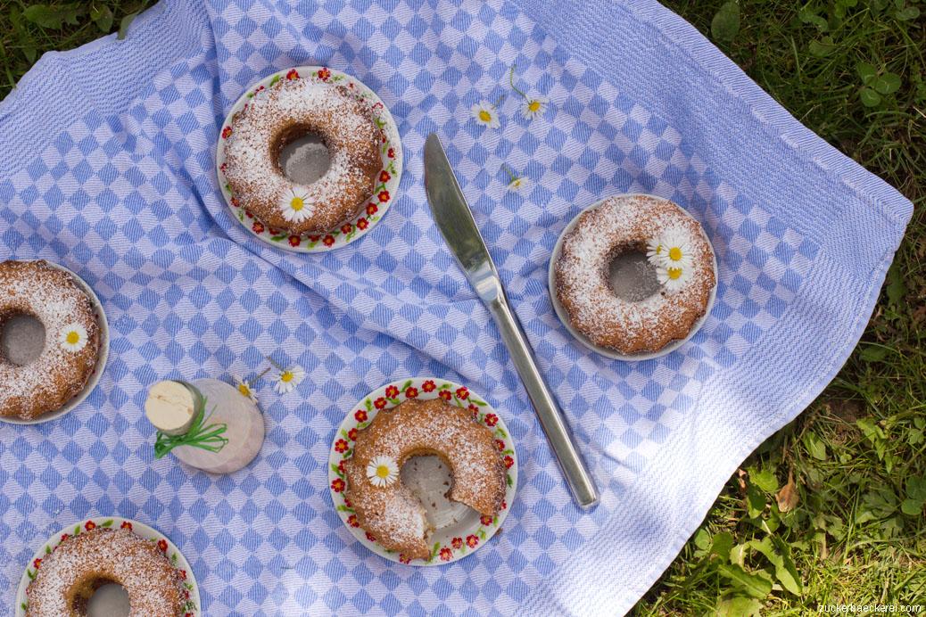 fünf kleine guglhupfs auf einer blauen tischdecke im gras