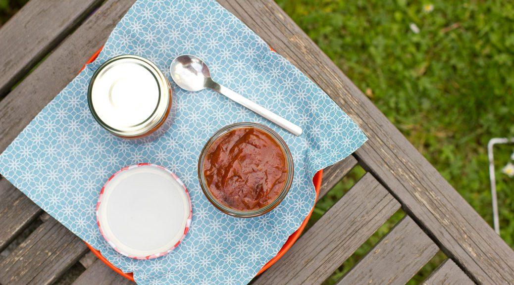 zwei gläser rhabarber-bbq-sauce von oben auf einer bank in der wiese, eines offen