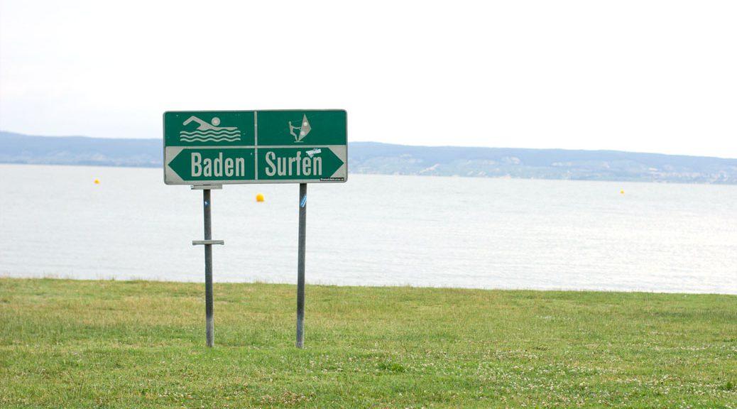 """schild """"baden surfen"""" auf einer wiese am ufer des neusiedlersees"""