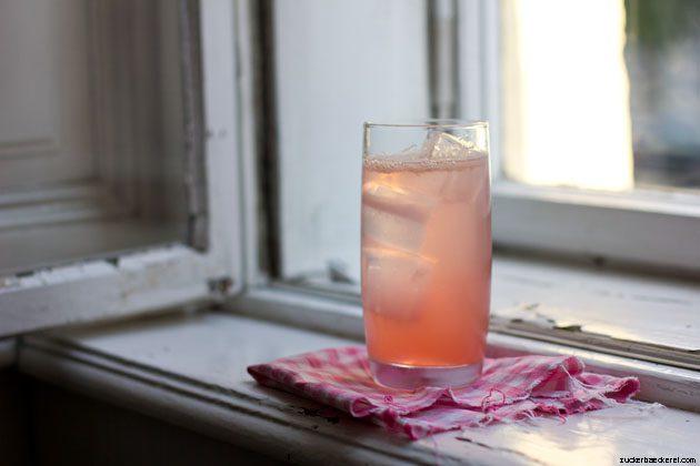 Ein Glas Rhabarber Vanille Fizz auf einem pink-weiß-karierten Stofffetzen auf einem Fensterbrett