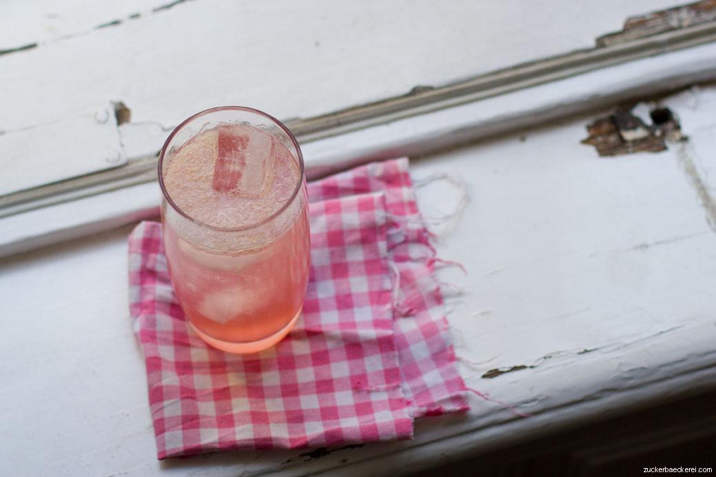 rhabarber vanille fizz auf einem rosa-weiß-karierten tuch, halb schräg von oben fotografiert
