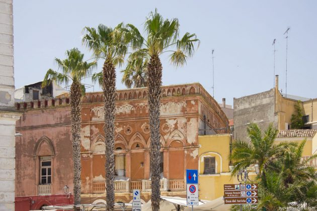 Drei Palmen vor einem orangen Gebäude, bei dem der Putz abbröckelt, blauer Himmel