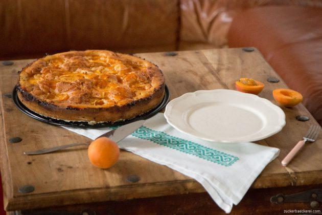 marillen-mascarpone-kuchen auf einem türkisen deckchen, daneben teller, tortenheber und gabel