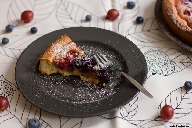 ein stück stachelbeer-frangipane-tarte mit puderzucker auf einem dunklen teller