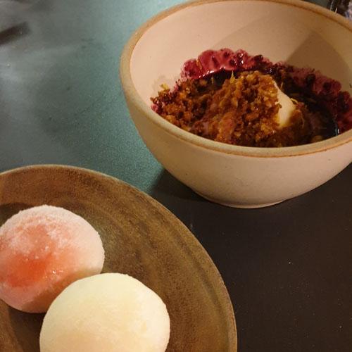 2 mochi bällchen und eine schüssel mit eis und walnusscrumble