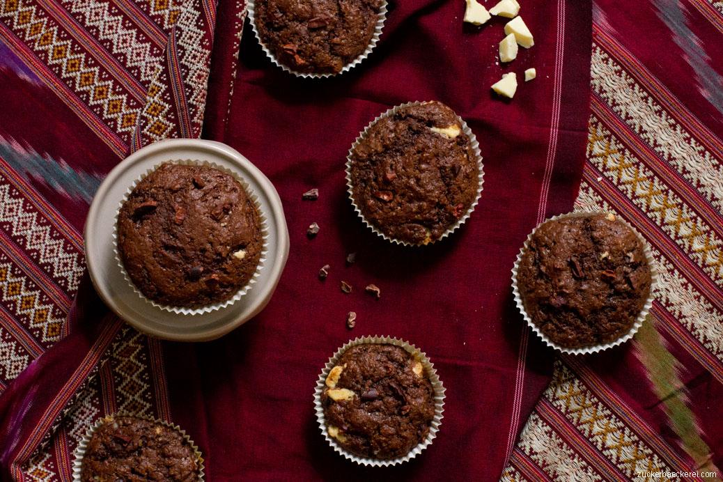 fünf Muffins auf dunkelrot gemusterter Tischdecke, vogelperspektive