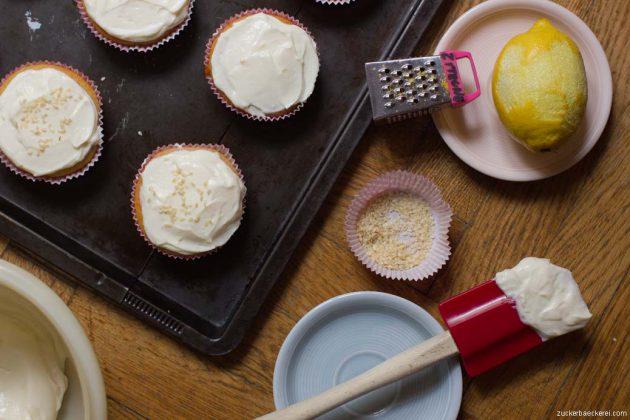 cupcakes mit frosting, daneben eine zitrone mit zitronenreibe, ein silikonspatel mit frosting und ein kleines schüsselchen mit sesamsamen, vogelperspektive