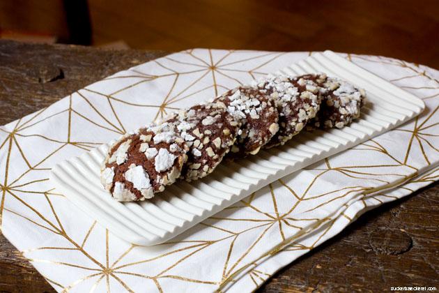 cookies auf einer rechteckigen weißen platte auf weiß-goldenem stoff