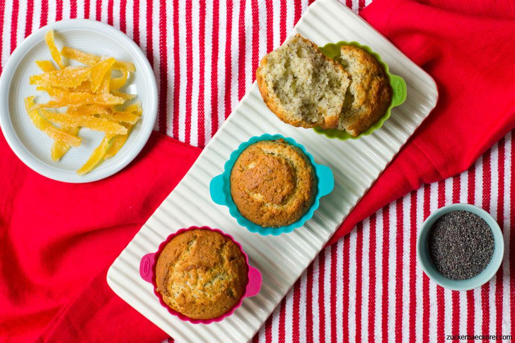 drei muffins, daneben ein teller mit kandierter zitrone und ein schälchen mit mohn, auf rot-weißem untergrund