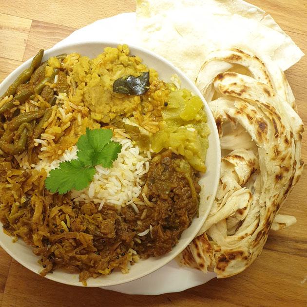 ein teller mit reis und verschiedenen currys außenherum, daneben fladenbrot