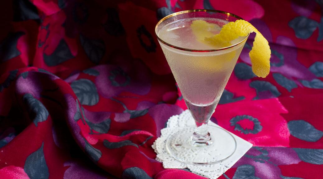 martiniglas mit leicht trübem hellen cocktail und einer zitronenzeste, im hintergrund eine grob geblümte tischdecke