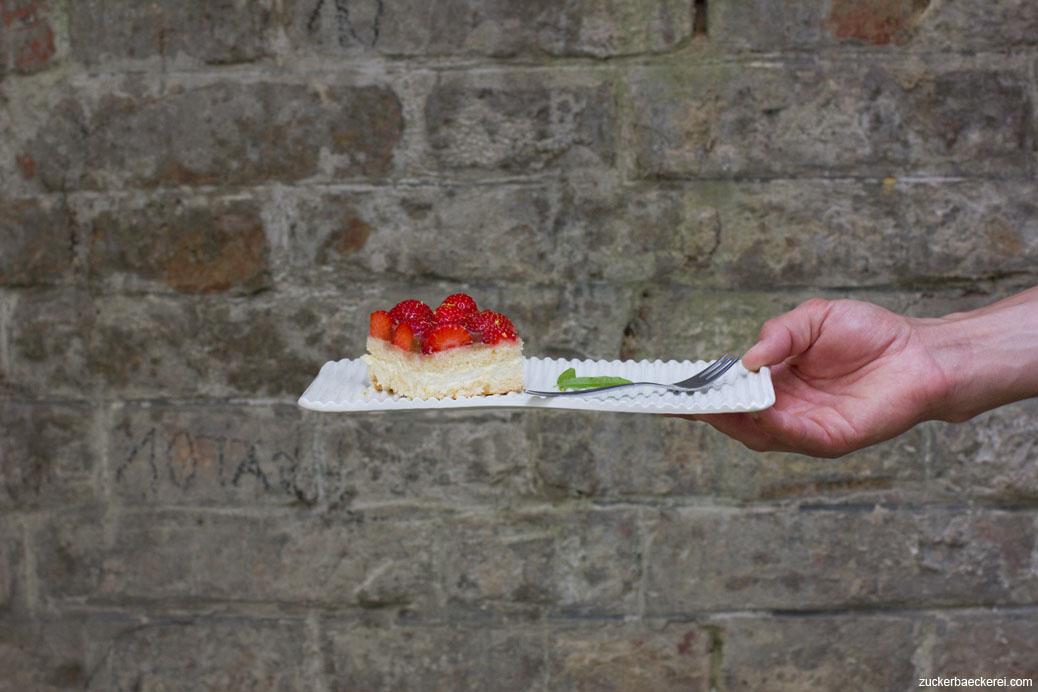 erdbeer-verbenen-kombucha-schnitten auf einem rechteckigen teller, von einer hand ins bild gehalten