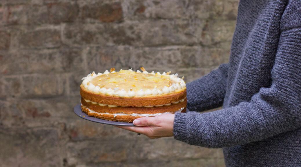 jana hält ihre torte vor einer grauen ziegelwand
