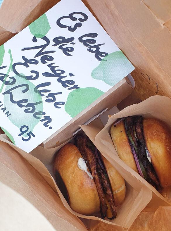 Zwei vegane Burger und Tian-Bistro-Postkarte in einem Papiersackerl
