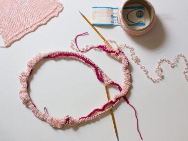 Rundstricknadel mit ein paar gestrickten Reihen in rosa satin Garn