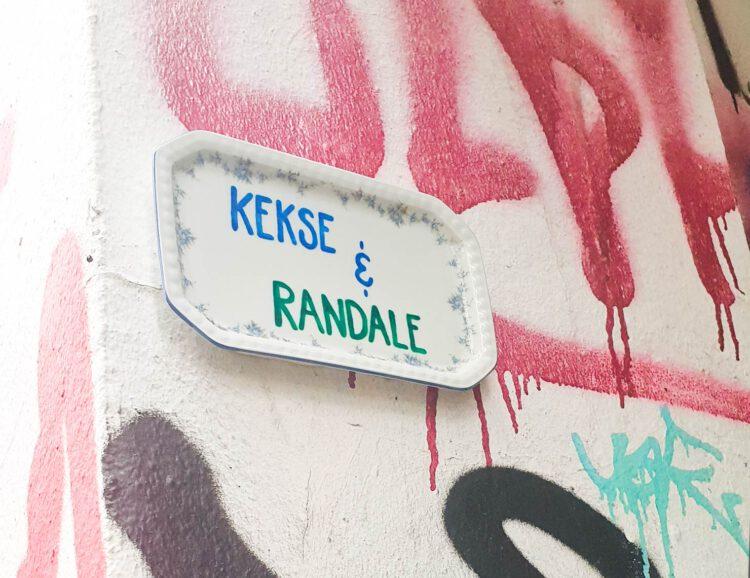 """Teller mit der Beschriftung """"Kekse & Randale"""" an einer Graffiti-Wand"""
